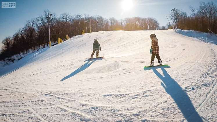 Two people snowboarding at Mountain Creek in Vernon, New Jersey